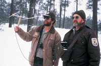 Two biologists locating a collared wolf with radio telemetry.